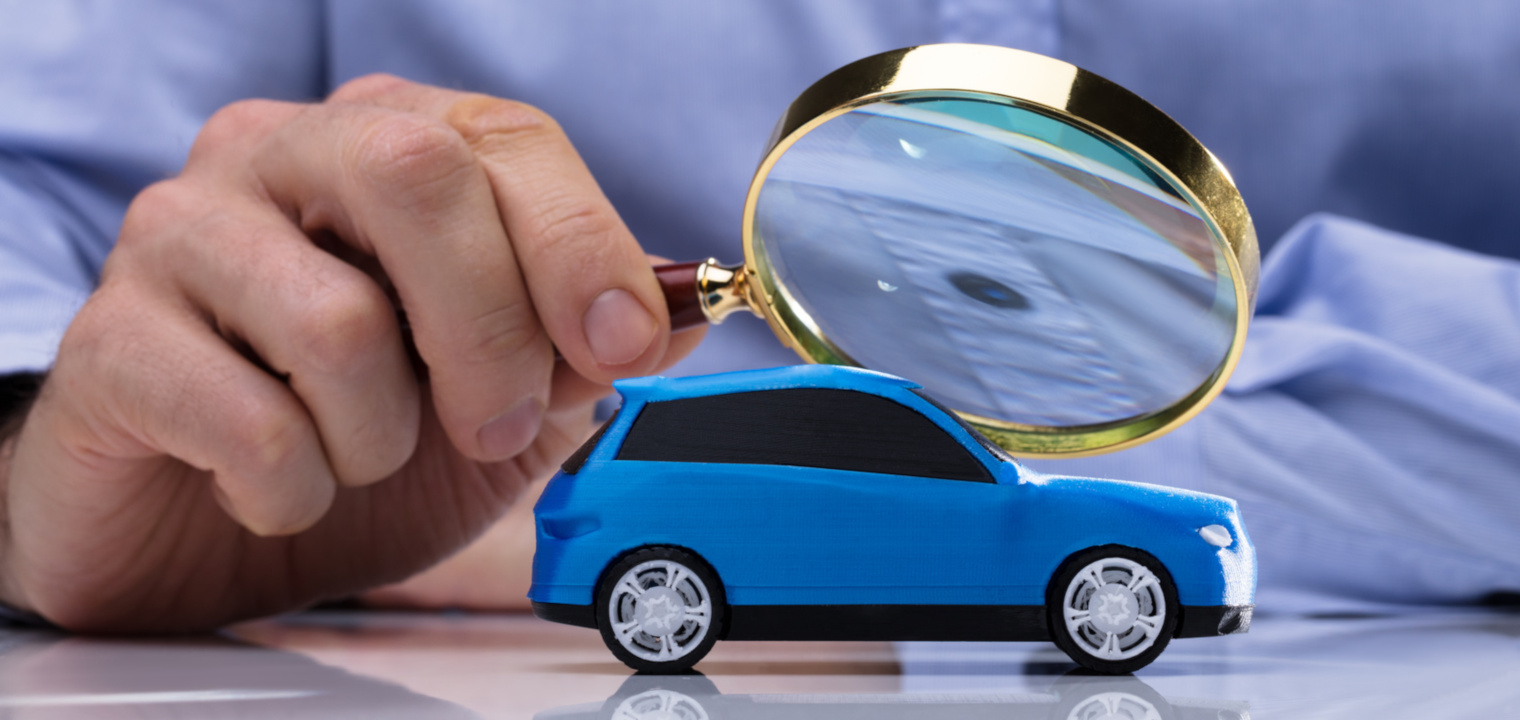 Close-up Of A Person's Hand Holding Magnifying Glass Over Small Blue Car
